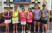 Six girls holding trophies from a tennis tournament