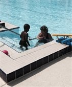 An instructor teaching a little boy how to swim.