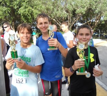 Three older boys holding trophies at the Gardens Splash and Dash