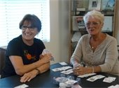 Two ladies sitting at a table and smiling while playing cards