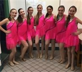 Seven girls standing in dance costumes