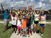 A group of kids and counselors from camp jumping with their hands up