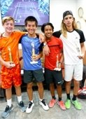 Four older boys holding trophies after a junior tennis tournament.