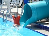 A girl coming out of a water slide into the pool