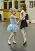 Two little girls holding hands and dancing