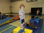 "A young boy standing on a balance beam doing a ""thumbs up""."