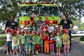 Two firefighters with a group of small children in front of a fire truck