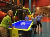 A counselor and three kids playing air hockey on a field trip