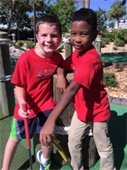Two young boys on the miniature golf course.