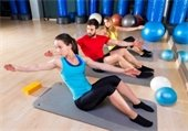 Two women and a man sitting on mats doing Pilates