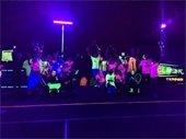 A group of tennis players under black lights at the XGLOsive tennis event.