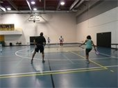 A man and three women playing pickleball