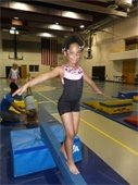 A young girl standing on a balance beam