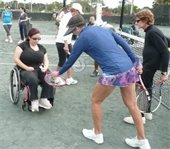 A tennis instructor teaching a special needs participant to play tennis