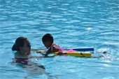 A swim instructor and young girl taking swim lesson
