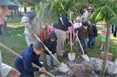 Young children shoveling dirt onto tree roots