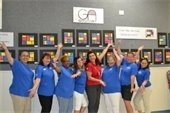 Riverside Youth Enrichment Center staff in front of children's artwork