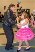 A dad and daughter dancing together