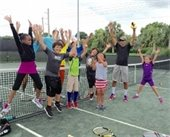 A group of children and their instructors jumping up on a tennis court.