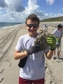 A teenage boy holding a piece of coral on a beach