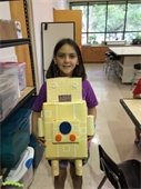 Girl holding a robot made from cardboard boxes