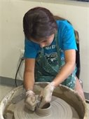 A girl working with clay on a potter's wheel