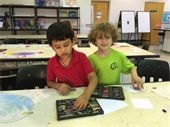 Two young boys working with pastels in art class