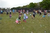 Children hunting for plastic eggs on a baseball field
