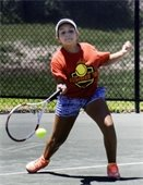 A teenage girl hitting a tennis ball with a tennis racket.