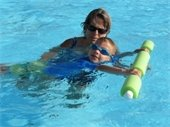A female instructor teaching a little boy swim lessons