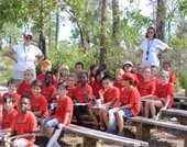 A group of campers and two counselors sitting on benches at Jonathan Dickinson State Park