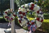 Two red, white and blue floral wreaths with ribbons