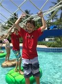 A boy holding ropes and balancing on a platform in a pool