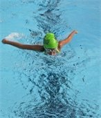 A child swimming in a pool with a swim cap on