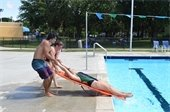 Three lifeguards practicing live saving skills