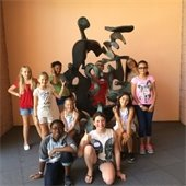 Youth campers surrounding a sculpture