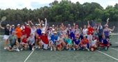 A group of men and women on the tennis court from the Hitting Frenzy class