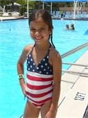 A young girl standing in front of a pool in a stars and stripes bathing suit
