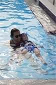 A swim instructor teaching a young boy swim lessons