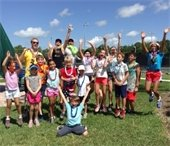 A group of boys and girls jumping in the air at camp.