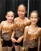 Three young girls in dance costumes