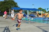 A young boy running from the pool in the Splash and Dash event
