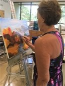 A woman standing and painting at an easel