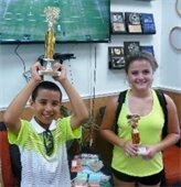 A boy and a girl holding tennis trophies