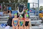 Girls on the swim team sitting around the shark mascot