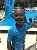 A young boy standing in front of a pool