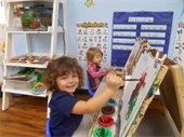 Two young children painting on easels