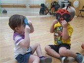 Two young children wearing bug masks
