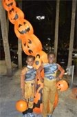 Two boys in costume standing in front of inflatable pumpkins