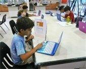 Children working on laptop computers in Robotics class